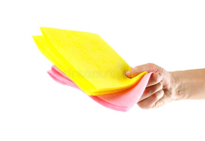 Ręki mienia menchii i koloru żółtego łachmany z bliska odizolowywający na białym b obraz royalty free