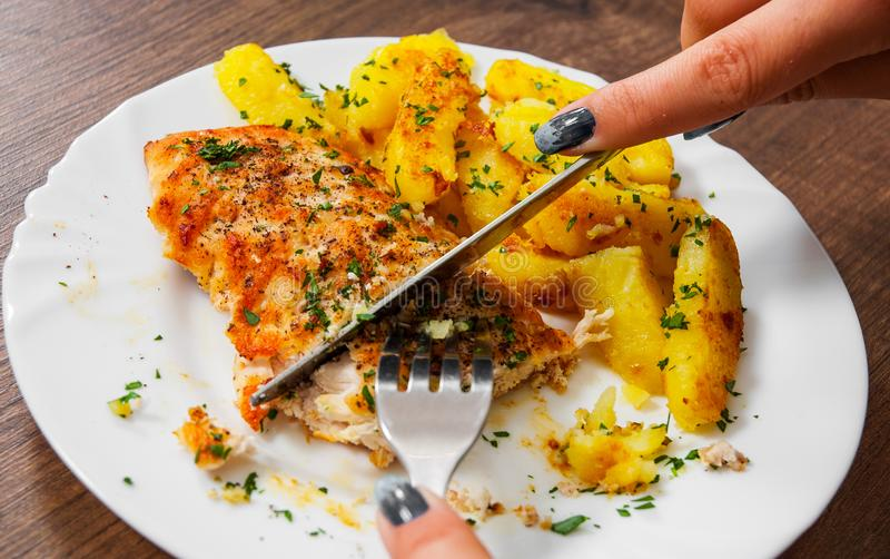 Ręki mienia nóż z Piec na grillu kurczak piersią z grulą w talerzu na drewnianym tle i rozwidlenie zdjęcie royalty free