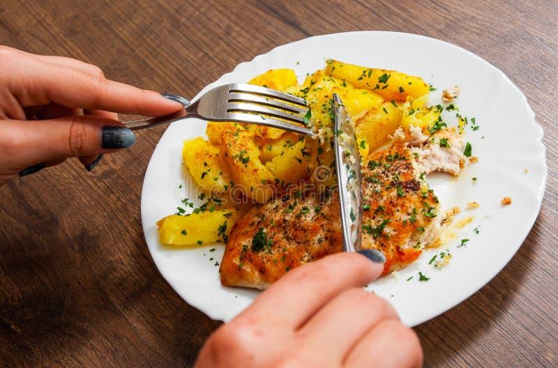 Ręki mienia nóż z Piec na grillu kurczak piersią z grulą w talerzu na drewnianym tle i rozwidlenie fotografia stock