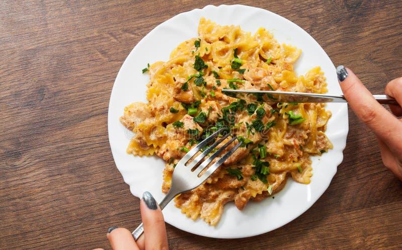 Ręki mienia nóż z Pokrojonym pieczonym kurczakiem polędwicowym w śmietankowym kumberlandzie i rozwidlenie z farfalle makaronem w  zdjęcie stock
