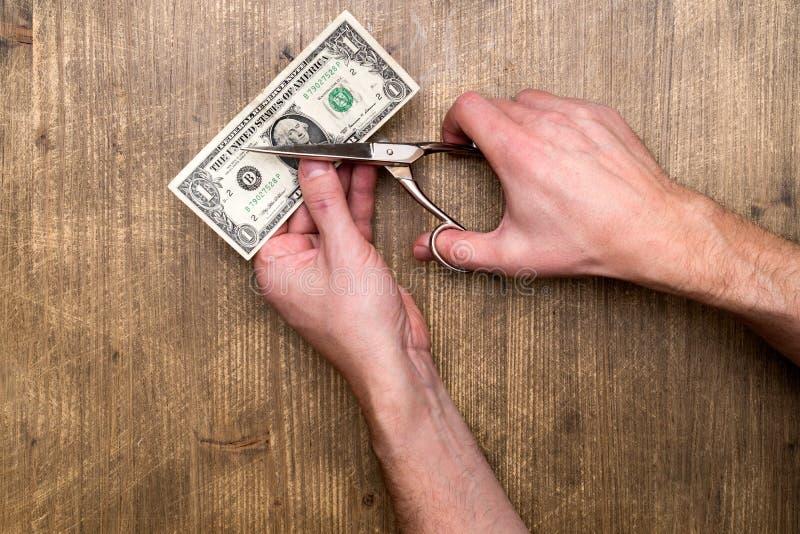 Ręki mienia nożyce ciie dolara amerykańskiego banknot fotografia stock