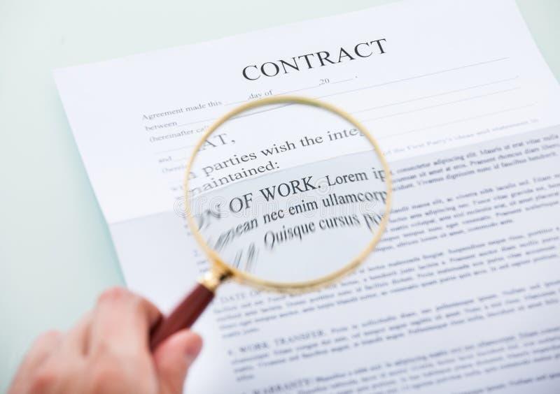 Ręki mienia powiększać - szkło nad kontraktem obraz stock