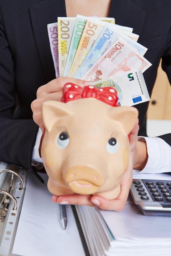 Ręki mienia prosiątka euro i bank obrazy royalty free