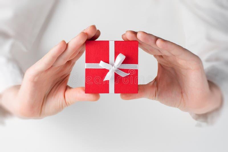 Ręki mienia pudełko dla prezenta na bielu obraz royalty free