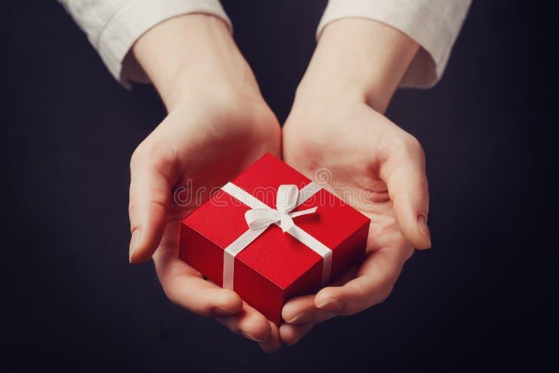 Ręki mienia pudełko dla prezenta odizolowywającego na czerni obraz royalty free