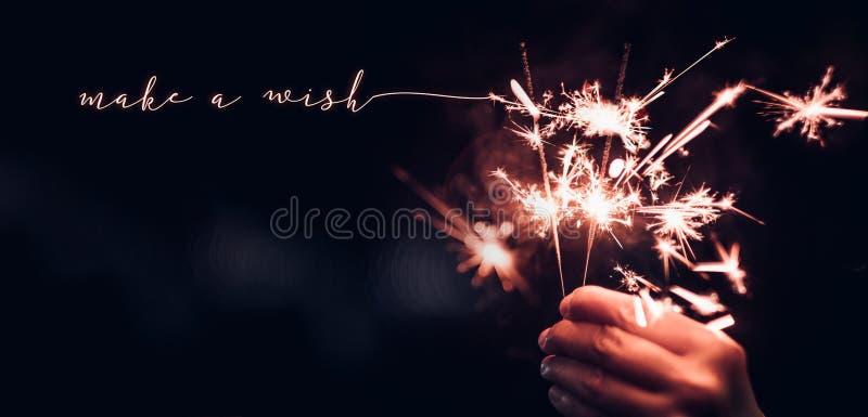 Ręki mienia Sparkler płonący wybuch z robi życzenia słowu na b fotografia stock