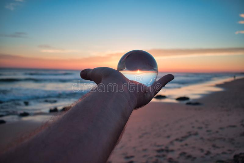Ręki mienia Szklanej piłki perspektywy plaży zmierzchu okręgu abstrakta krajobrazu Piękny kryształ zdjęcie stock