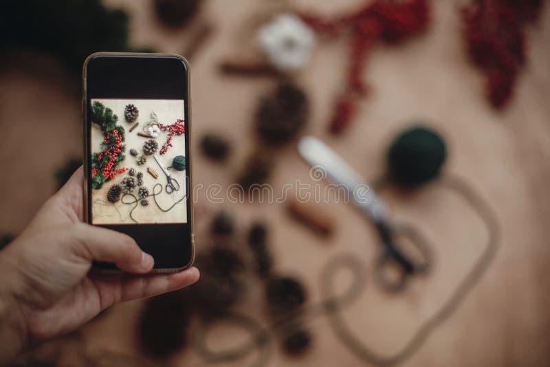 Ręki mienia telefon i brać fotografia nieociosany boże narodzenie wianek f zdjęcia stock