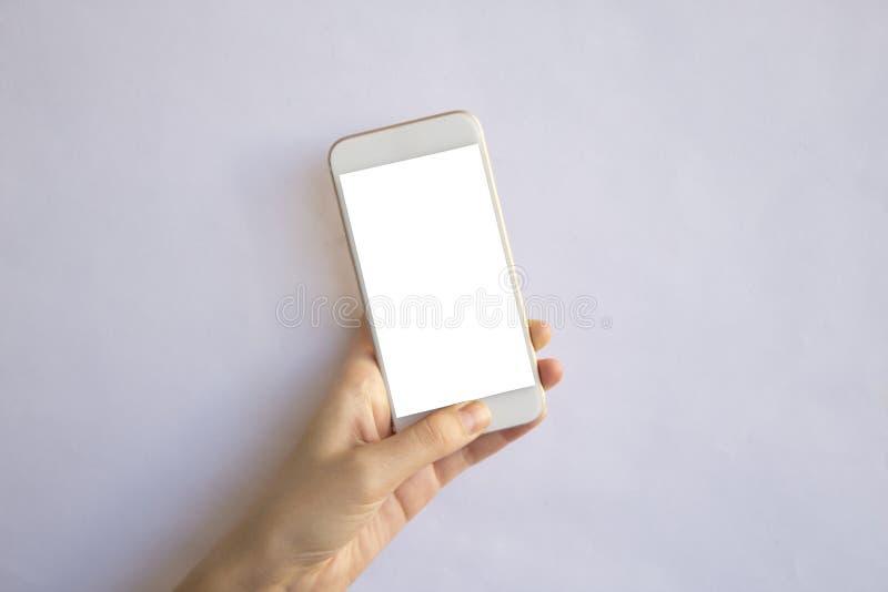 Ręki mienia telefon komórkowy z odosobnionym tłem fotografia royalty free