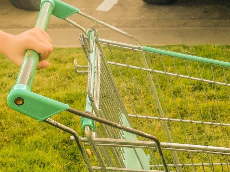Ręki mienia wózek na zakupy z zielonej trawy tłem obraz stock