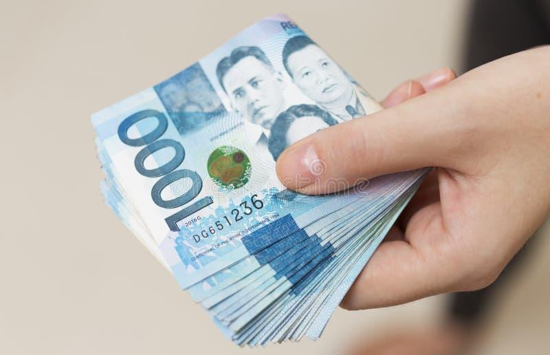 Ręki mienie składał plika błękitny pieniądze w gotówce tysiąc Filipiny peso Dawać łapówce, płacący rachunki lub dostawać pensję P fotografia royalty free
