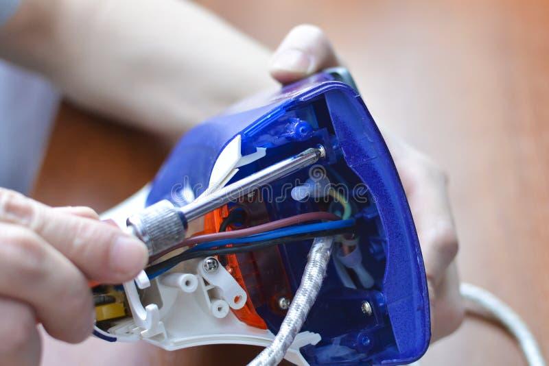 Ręki naprawy żelazo Pojęcie: domowego urządzenia naprawa obrazy royalty free