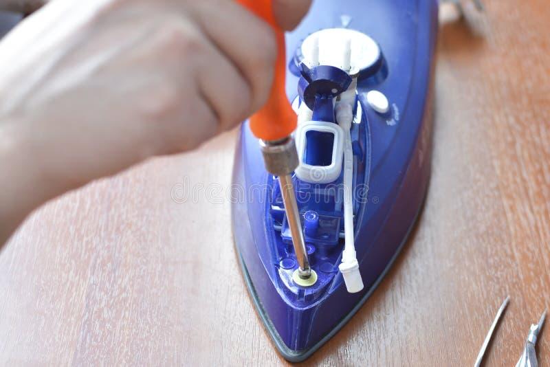 Ręki naprawy żelazo Pojęcie: domowego urządzenia naprawa zdjęcie royalty free