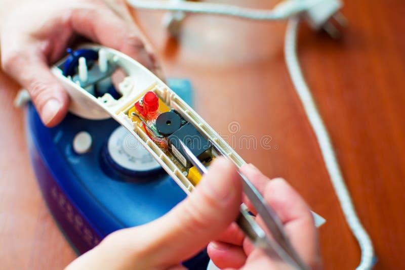 Ręki naprawy żelazo Pojęcie: domowego urządzenia naprawa, remontowe usługi fotografia stock