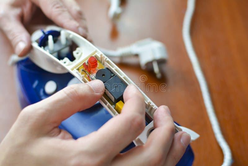 Ręki naprawy żelazo Pojęcie: domowego urządzenia naprawa, remontowe usługi zdjęcia royalty free