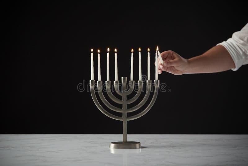 Ręki Oświetleniowa świeczka Na metalu Hanukkah Menorah Na marmur powierzchni Przeciw Czarnemu Pracownianemu tłu zdjęcia stock