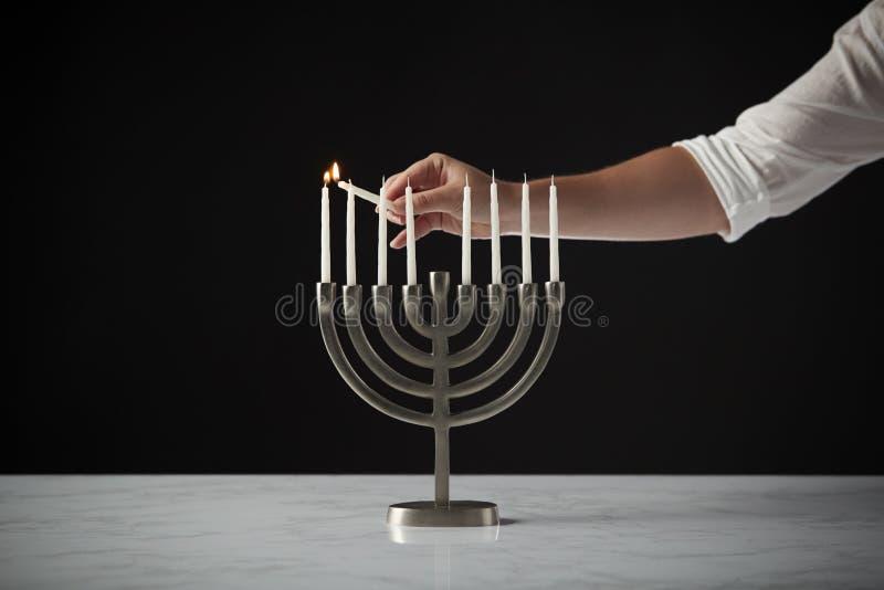 Ręki Oświetleniowa świeczka Na metalu Hanukkah Menorah Na marmur powierzchni Przeciw Czarnemu Pracownianemu tłu fotografia royalty free