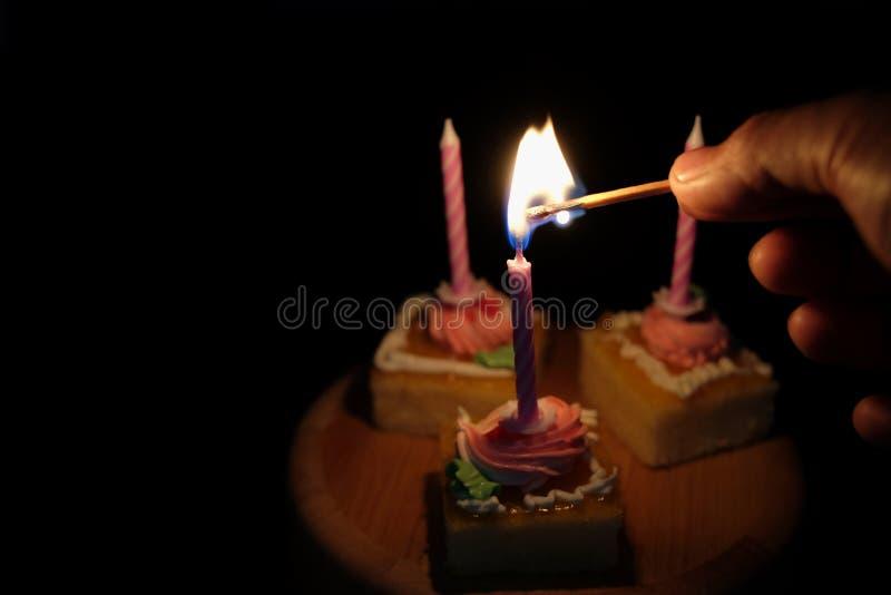 Ręki oświetleniowa świeczka na torcie w ciemnym brzmieniu zdjęcia royalty free