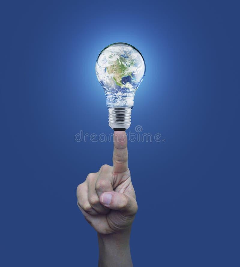 Ręki odciskania ziemi kula ziemska w żarówce nad błękitnym tłem, En zdjęcie royalty free