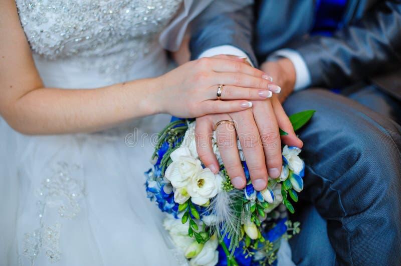 Ręki państwo młodzi kłama na bridal z pierścionkami obraz stock