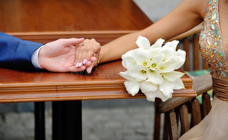 Ręki państwo młodzi na tle ślubny bouq zdjęcia royalty free