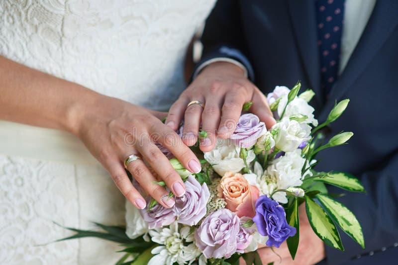 Ręki państwo młodzi z pierścionkami na ślubnym bukiecie fotografia stock