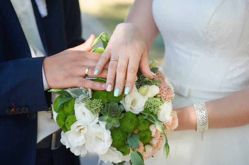 Ręki państwo młodzi z złocistymi pierścionkami na ślubnym bukiecie zdjęcie royalty free