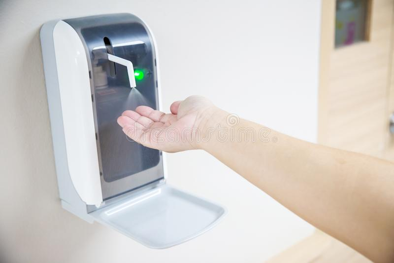 ręki pod automatyczną alkohol aptekarką zdjęcia stock