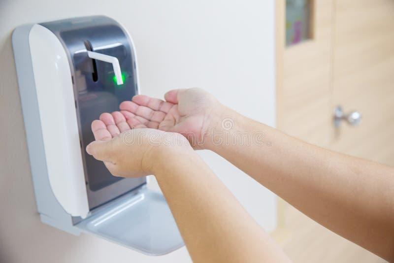 2 ręki pod automatyczną alkohol aptekarką zdjęcia royalty free