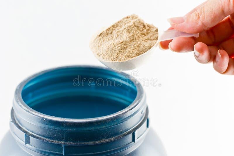 Ręki podwyżka łyżkowa miara serwatki czekolady proteinowego proszka dla zdjęcia royalty free