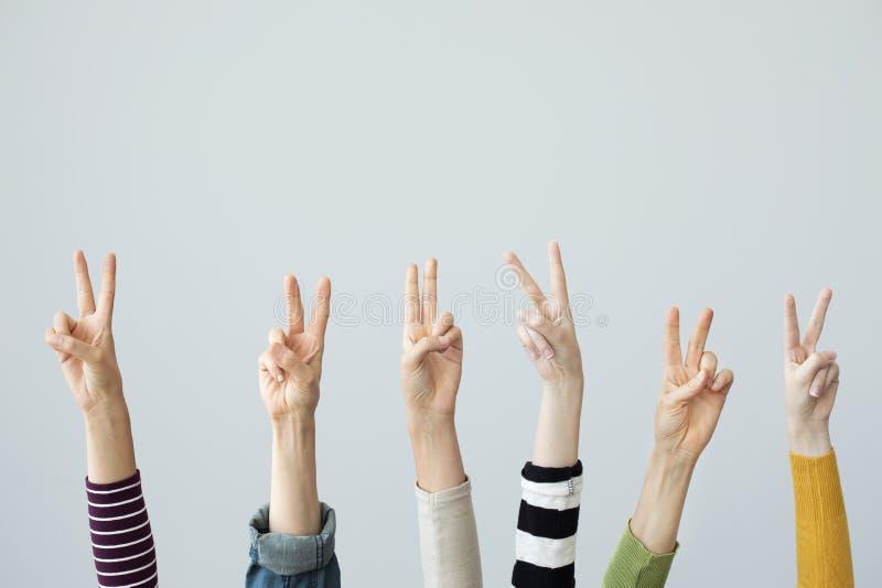 Ręki pokazuje zwycięstwo znaka na popielatym tle obraz royalty free