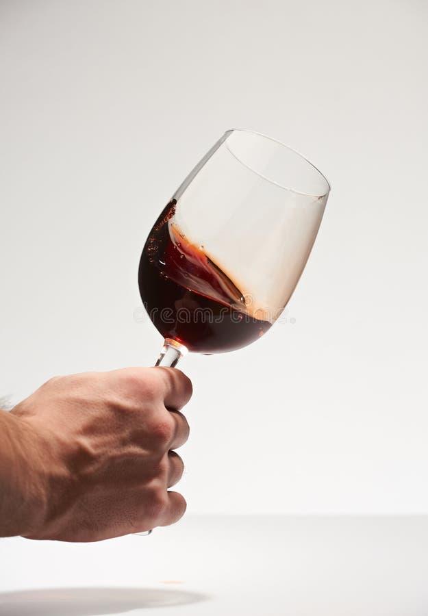 Ręki potrząsalny szkło z czerwonym winem fotografia stock