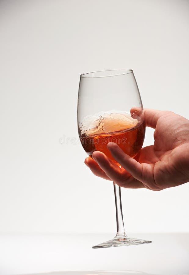 Ręki potrząsalny szkło z czerwonym winem obraz stock