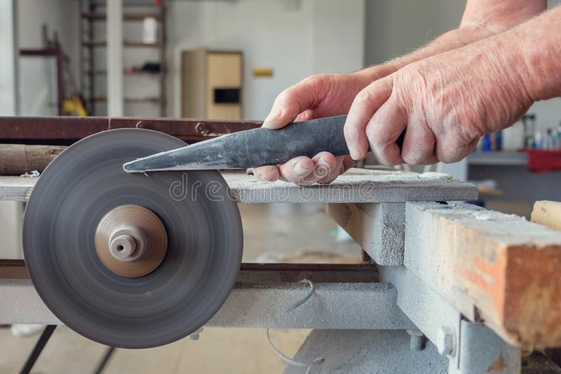 Ręki pracownik który sharpering nóż na toczaku fotografia royalty free
