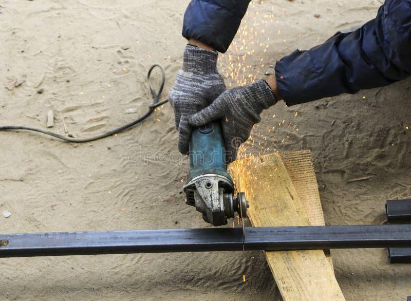 Ręki pracownik w rękawiczkach cią metal drymby z grindin obrazy stock