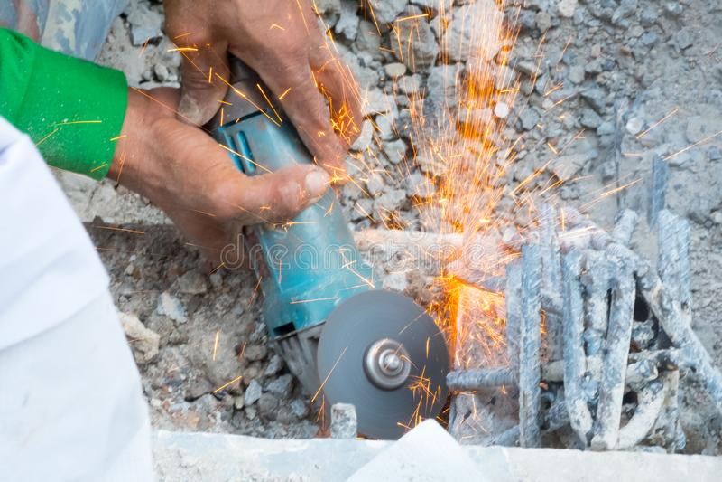 Ręki pracownika metalu rżnięty żelazo z szlifierską maszyną obrazy royalty free