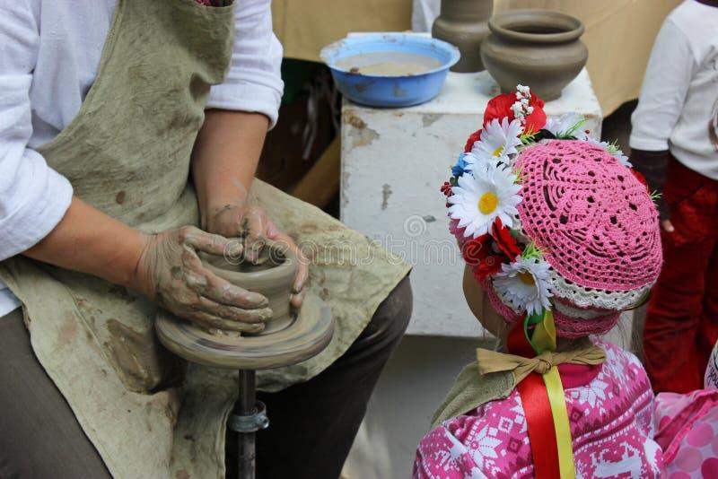 Ręki pracuje na ceramicznym kole i dziewczynie troszkę fotografia royalty free