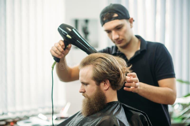 Ręki robi ostrzyżeniu atrakcyjny brodaty mężczyzna w zakładzie fryzjerskim młody fryzjer męski obrazy stock