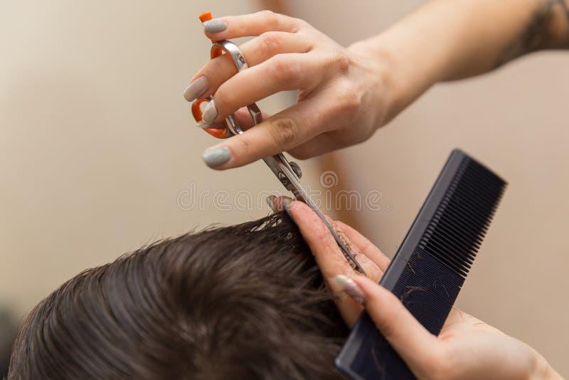 Ręki robi ostrzyżeniu atrakcyjny mężczyzna w zakładzie fryzjerskim młody fryzjer męski zdjęcie stock