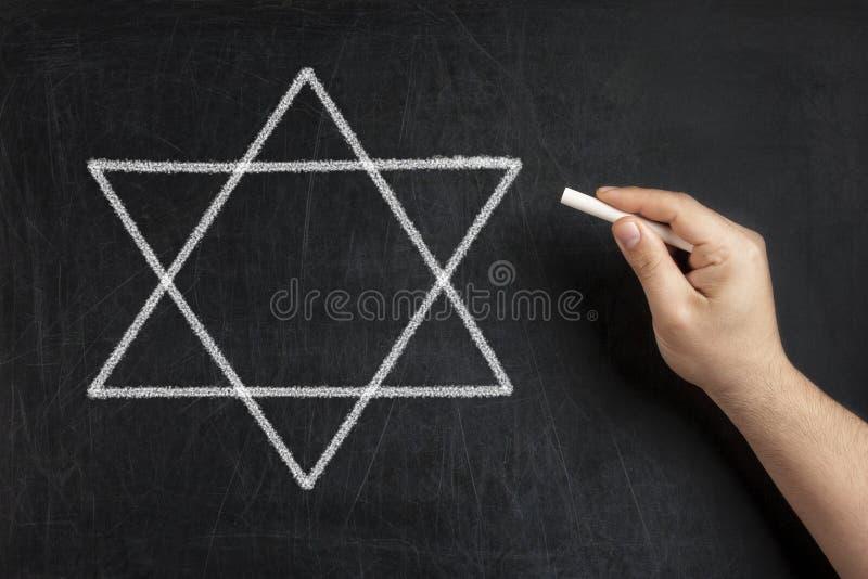 Ręki rysunkowa gwiazda dawidowa na blackboard lub chalkboard obrazy stock