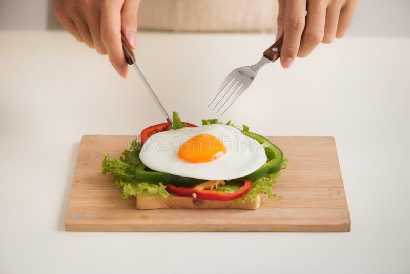 Ręki słuzyć z mężczyzny cięcie jajka na tnącej desce, chleba, ziele, kiełbasianego i świeżego sokiem, fotografia stock