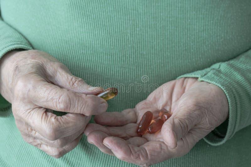 Ręki senior kobiety mienia witaminy pigułki na jej palmie obraz royalty free