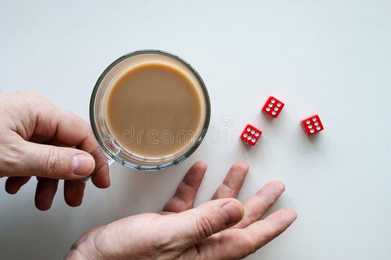 Ręki stacza się czerwonych kostka do gry sześć fok, szklany kubek kawa, odosobniony tło, odgórny widok obrazy stock