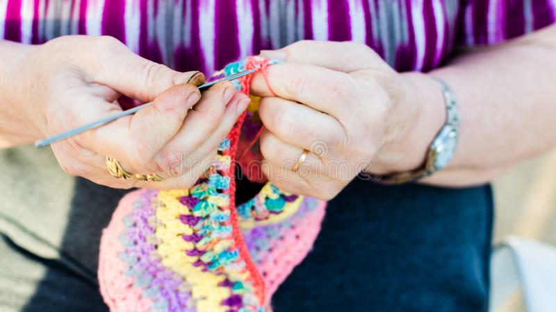 Ręki starej damy dzianie na dziewiarskich igłach, używać kolorową wełnę fotografia stock