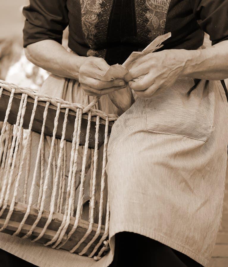 ręki starsza kobieta podczas gdy tworzący słomianą torbę z sepiowym zdjęcia stock