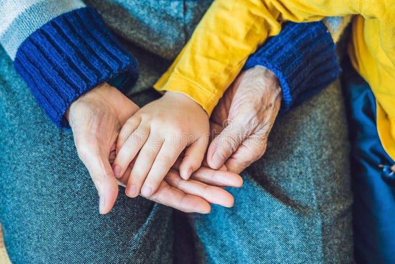 Ręki starsza osoba i ręki dziecko przeciw obrazy stock