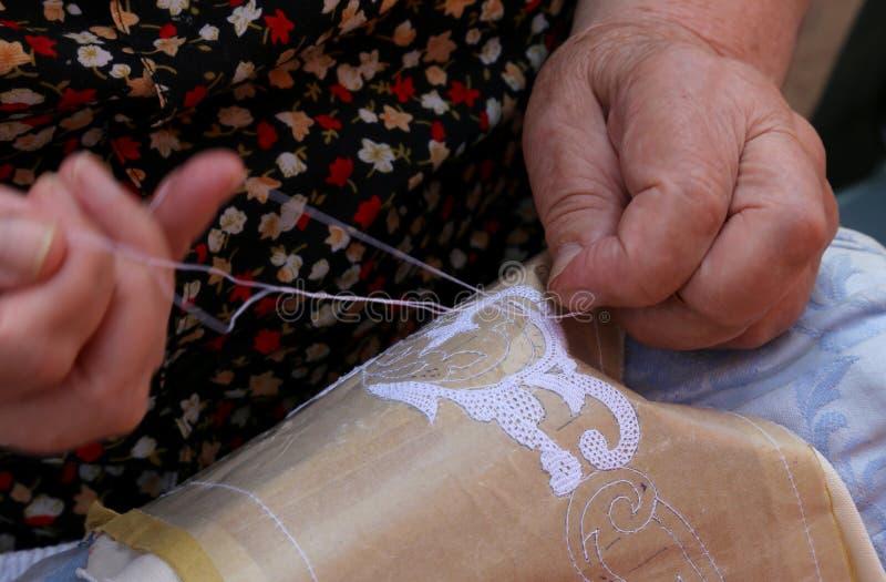 Ręki starszej osoby kobieta haftuje koronkę z tombolo i c fotografia royalty free