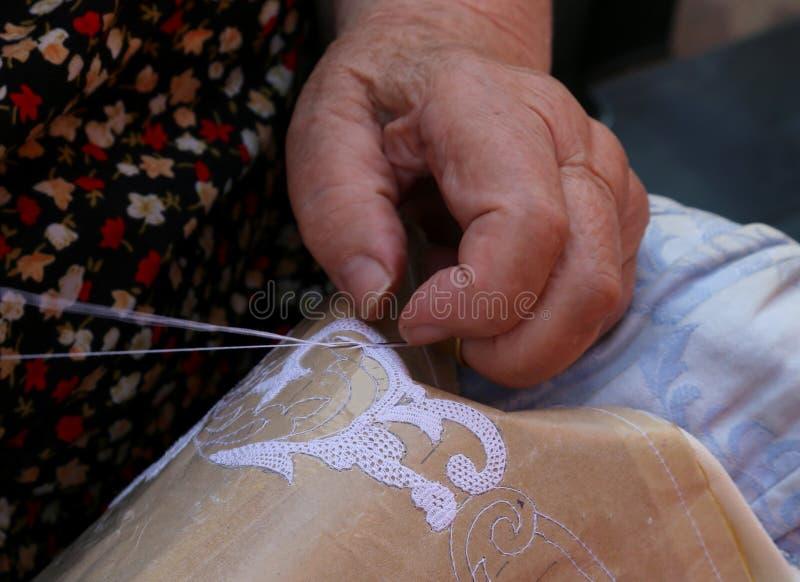 Ręki starszej osoby kobieta haftuje koronkę z tombolo i c zdjęcia royalty free