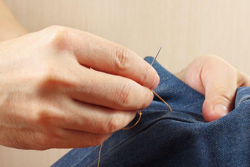 Ręki sukiennik szą drelichową tkaninę z igły zakończeniem up zdjęcia stock