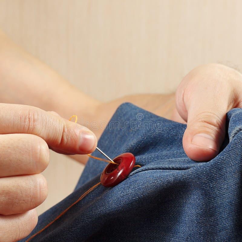 Ręki sukiennik szą guzika drelichowy tkaniny zakończenie up fotografia stock